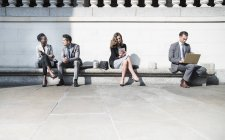 Les gens d'affaires d'entreprise travaillant sur un banc ensoleillé en plein air — Photo de stock