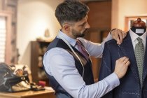 Tailor adjusting suit on dressmakers model in menswear shop — Stock Photo