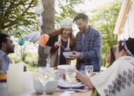 Couple serving lunch to friends at patio table — Stock Photo