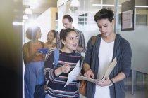 College students discussing homework in corridor — Stock Photo