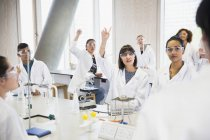 College students raising hands in science laboratory classroom — Stock Photo