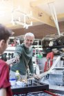 Smiling father taking tool from son in auto repair shop — Stockfoto