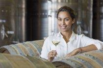 Portrait confident vintner drinking white wine in winery cellar — Stock Photo