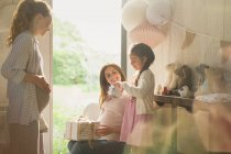 Daughter opening gift with pregnant mother — Stockfoto