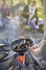 Friends cooking hot dogs over campfire — Stock Photo