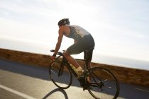Male triathlete cyclist cycling on sunny ocean road — Stock Photo