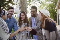 Friends toasting champagne glasses on patio — Stock Photo