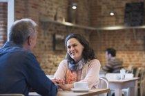 Ласкавим пара, тримаючись за руки говорити в кафе — стокове фото