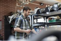Mechanic holding tool in auto repair shop — Stock Photo