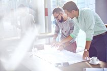 Architects reviewing blueprints in sunny office — Stock Photo