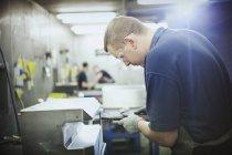 Работник с использованием оборудования на сталелитейном заводе — стоковое фото