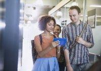 Студенти коледжу, використовуючи цифровий планшет, ходити в коридорі — стокове фото