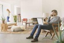 Мужчина разговаривает по мобильному телефону и использует ноутбук в гостиной — стоковое фото
