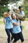 Determined woman running with log on boot camp obstacle course — Stock Photo