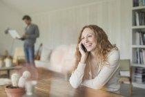 Улыбающаяся женщина разговаривает по телефону за обеденным столом — стоковое фото