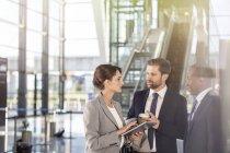 Empresários com tablet digital conversando no aeroporto — Fotografia de Stock