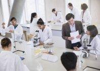 Professeur de sciences et étudiants utilisant des microscopes en salle de classe de laboratoire de sciences — Photo de stock
