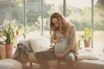 Улыбающаяся беременная женщина держит живот — стоковое фото