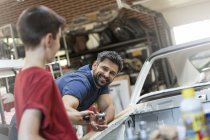 Улыбающийся отец забирает инструмент у сына в автомастерской — стоковое фото