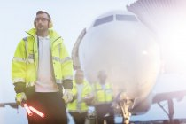 Air traffic controller standing in front of airplane on airport tarmac — Photo de stock