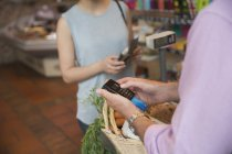 Grocery store clerk using credit card machine — Stock Photo