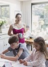 Mother with coffee watching daughter and son doing homework — Stock Photo