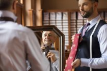 Tailor showing ties to businessman at mirror in menswear shop — Stock Photo