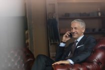 Smiling businessman talking on cell phone in menswear shop — Stock Photo