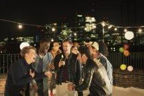 Jeunes hommes buvant et riant à la fête sur le toit — Photo de stock