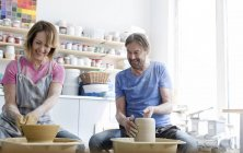Smiling mature couple using pottery wheels in studio — Stock Photo