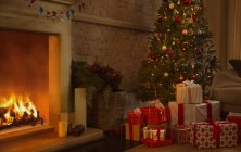 Christmas tree and gifts near fireplace in living room — Stock Photo