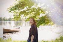 Porträt lächelnde Frau am sonnigen Seeufer — Stockfoto