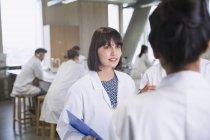 Студенти коледжу жіночої в лабораторію пальто говорити в classroom наукової лабораторії — стокове фото