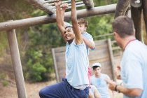 Man crossing monkey bars on boot camp obstacle course — Stock Photo