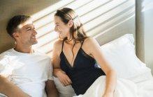 Усміхаючись пара розмова в ліжку разом — стокове фото