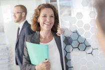 Portrait of woman holding documents standing at glass door, colleague in background — Stock Photo