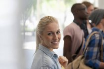 Улыбающаяся студентка смотрит в камеру с другими студентами в фоновом режиме — стоковое фото