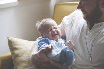 Отец держит и смотрит на плачущего ребенка — стоковое фото