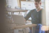 Бизнесмен работает на ноутбуке в офисе — стоковое фото