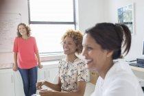 Три женщины смеются во время встречи в офисе — стоковое фото