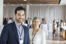 Portrait of man and woman standing in lobby of conference center smiling — Stock Photo