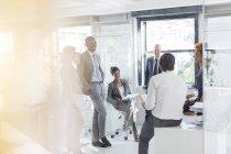 Des hommes d'affaires souriants se rencontrent dans un bureau moderne — Photo de stock