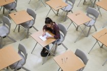 Elevated view of lone female student writing their GCSE exam in classroom — Stock Photo