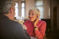 Vieux couple mutuellement le grillage avec le vin blanc — Photo de stock