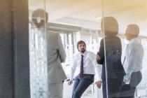 Gente che ha riunione in ufficio moderno visto attraverso la porta in vetro — Foto stock
