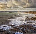 Vue panoramique du paysage de bord de mer avec des vagues qui s'écrasent sur la plage rocheuse — Photo de stock