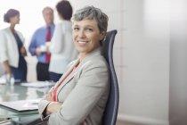 Портрет деловой женщины, сидящей в кресле с скрещенными руками в конференц-зале — стоковое фото