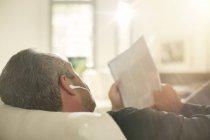 Homem mais velho escutando fones de ouvido no sofá — Fotografia de Stock