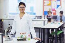 Ritratto di maestra sorridente con occhiali protettivi, in piedi dietro la scrivania con microscopio e provette in rack, studenti in background — Foto stock
