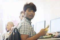 Учень, сидячи за столом, за допомогою мобільного телефону — стокове фото